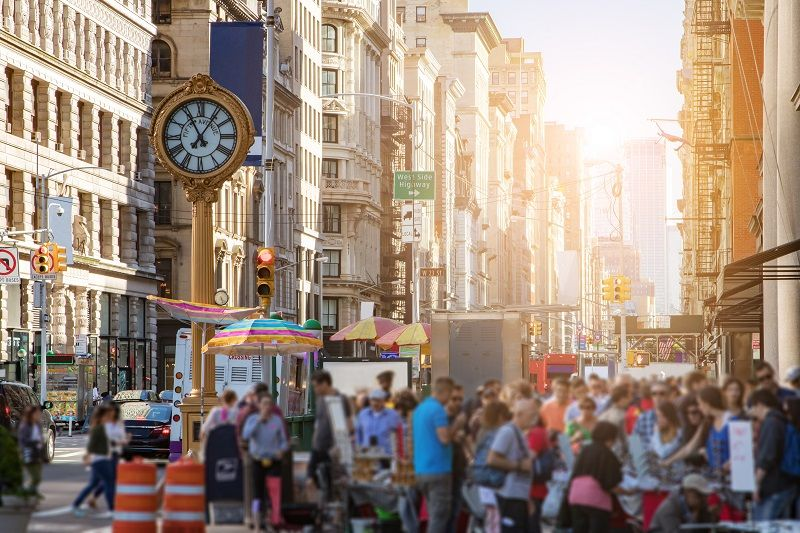 Sunlight shines on the buildings of Manhattan with crowds of people in New York City-cm