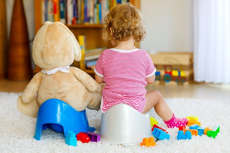 Closeup of cute little 12 months-old-toddler-baby-girl-child-sitting-on-potty.-Kid-playing-with-big-plush-soft-toy-cm
