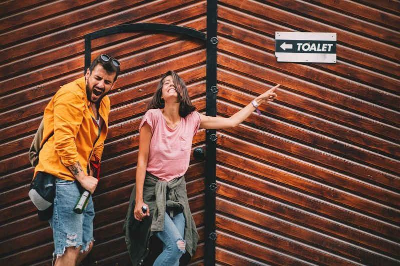 Young-couple-with-beer-in-hand-is-searching-for-a-public-toilet-on-the-street-cm