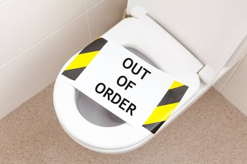 Household toilet with a sign that reads 'out of order'-cm
