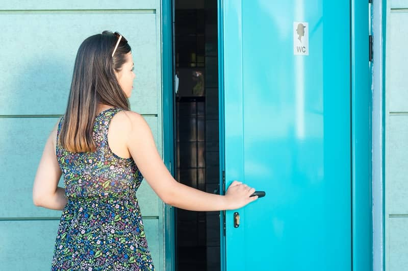 Young woman entering public toilet outside in park-cm