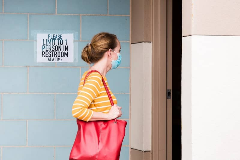 Woman wearing face mask waits to enter bathroom-cm