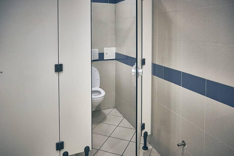 Open door of public toilet stall. Toilet bowl inside toilet stall-cm